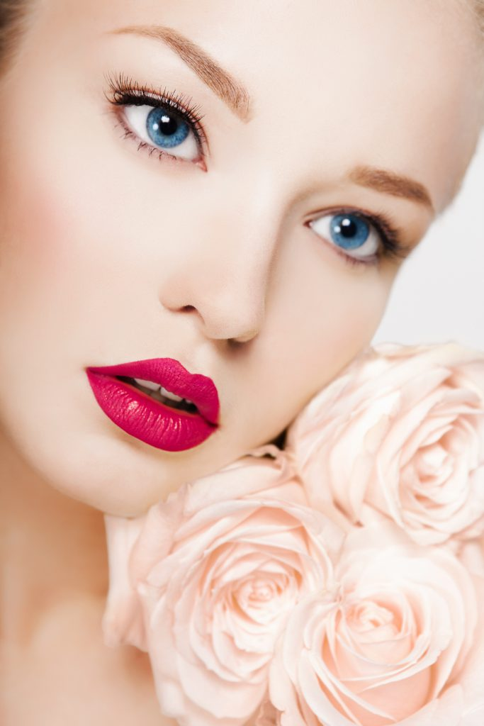 Beauty portrait of young model with roses, red lipstick make-up
